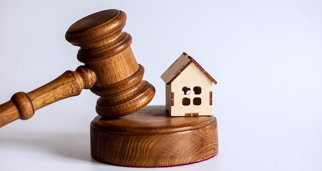 Hamer en houten huismodel voor het concept van de subprime leningcrisis