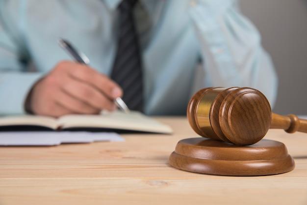 Hamer en rechter schrijft op papier op een grijze ondergrond