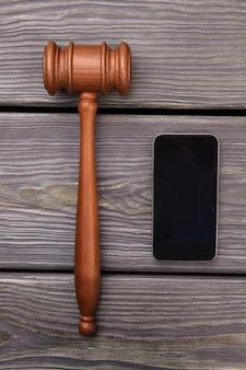 Hamer en smartphone op een grijs bureau.