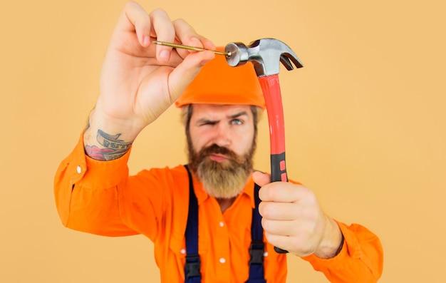 Hamer en spijkers. bouwer hameren spijker. reparateur met reparatiehulpmiddelen. selectieve aandacht.