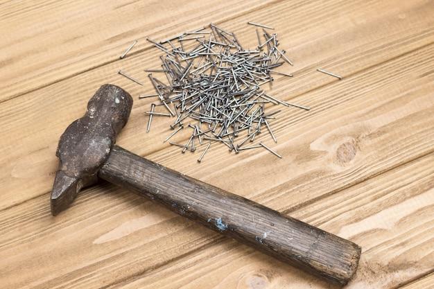 Hamer en spijkers op houten lichte achtergrond