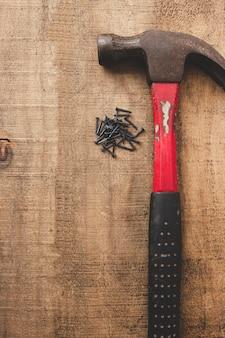 Hamer en zwarte nagels op houten tafel. oude tools. kopieer ruimte.