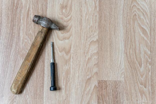 Hamer met houten handvat en platte schroevendraaier op houten vloer achtergrond met kopie afstandsstuk