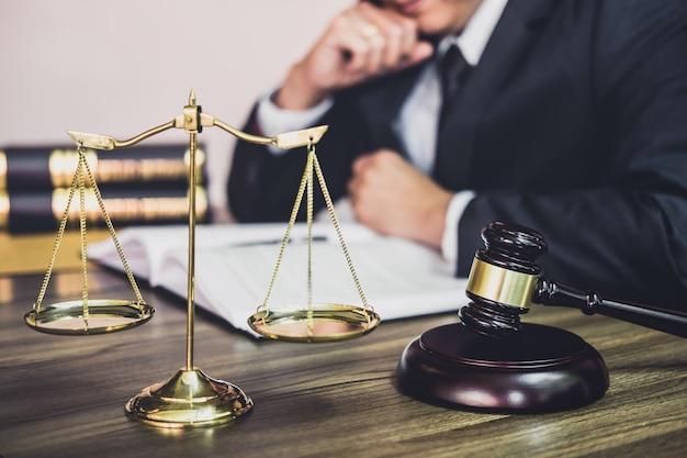 Hamer op houten lijst en adviseur of mannelijke advocaat die aan een document werkt