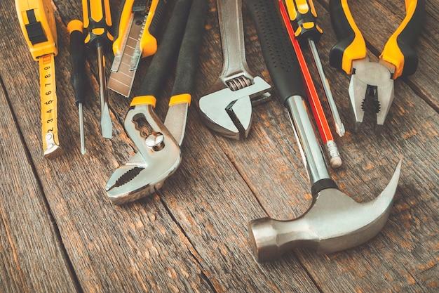 Hamer, schroevendraaier, tang, een mes, een sleutel en een rood potlood liggend op een houten plank