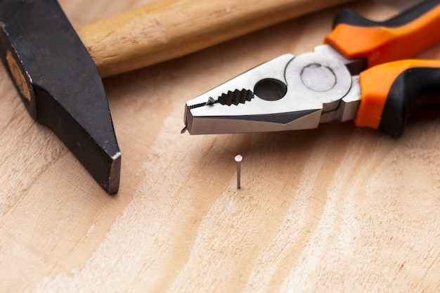 Hamer, spijkers en tangen liggen op een houten achtergrond. hulpmiddelen van de bouw selectieve focus