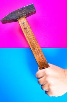Hamer voor reparatie in de hand op een kleurrijk of roze en blauw