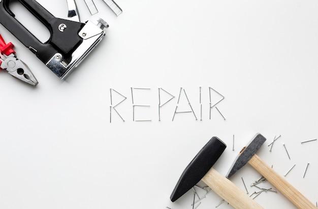 Hamers en reparatie woord geschreven met nagels