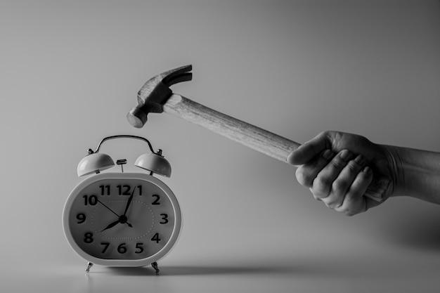 Hammer slaat voor het vernietigen van een wekker. strijd en tijdslimieten concept.