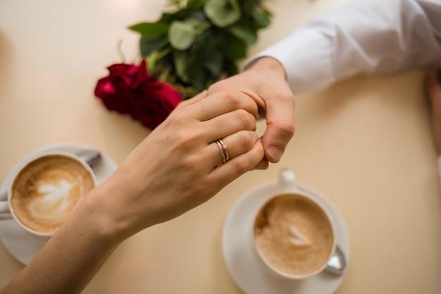 Hand aan een vrouw met een trouwring in haar hand aan een man op tafel