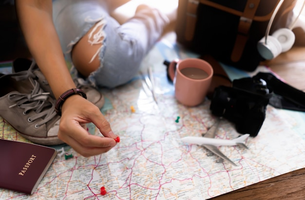 Hand aan het plannen van vakantiereis en accessoires voor op reis