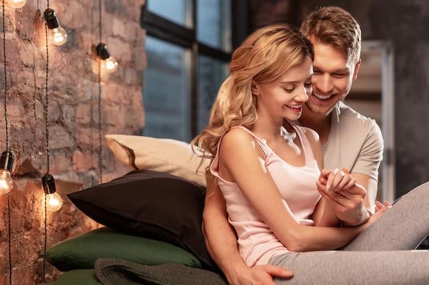 Hand aanraken. liefdevolle knappe bebaarde man glimlachend en ontroerende hand van zijn mooie vrouw