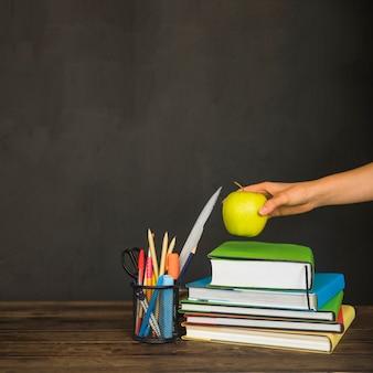 Hand appel aanbrengend studieboeken op de werkplek