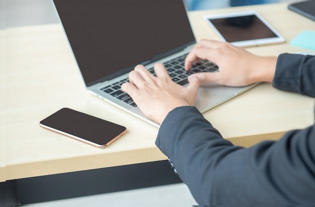 Hand aziatische zakenman die laptop op werkplaats met behulp van