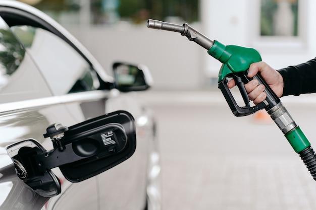 Hand benzinebrandstof pompen in auto bij benzinestation