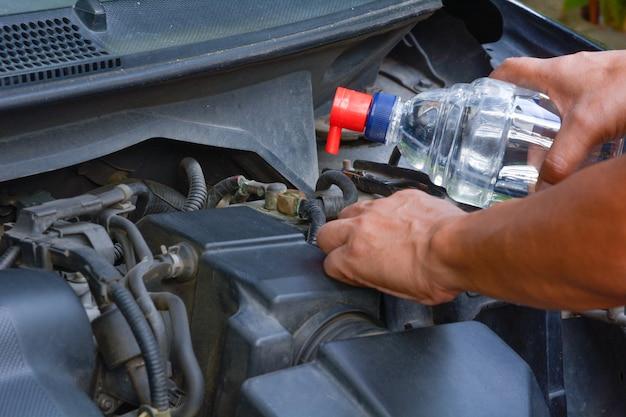 Hand bij de mens voeg de gedestilleerde waterbatterij toe voordat u de auto bestuurt.