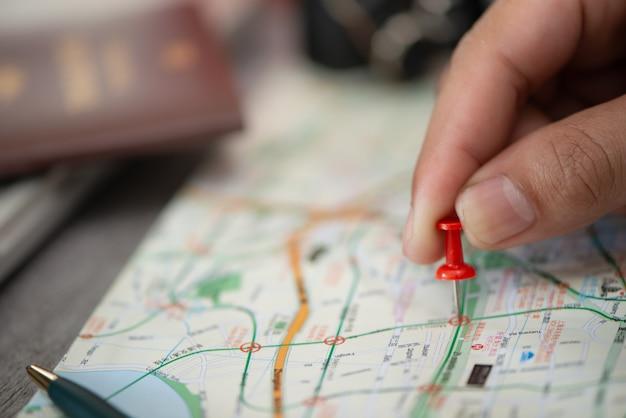 Hand bij het richten van rood speldplan om op kaart te reizen, reisconcept