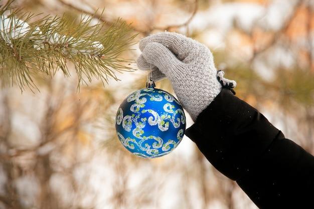 Hand blauw versierd kerstbal ornament op een kerstboom zetten