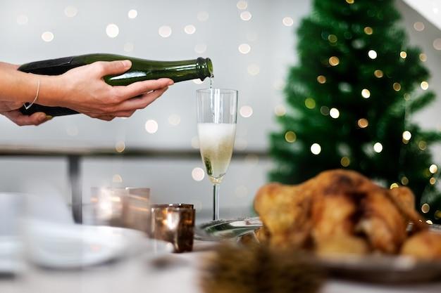 Hand champagne serveren op kersttafel selectieve focus op fles