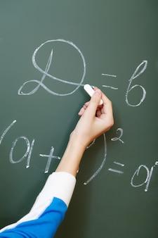 Hand close-up van de student schrijven met krijt op het bord