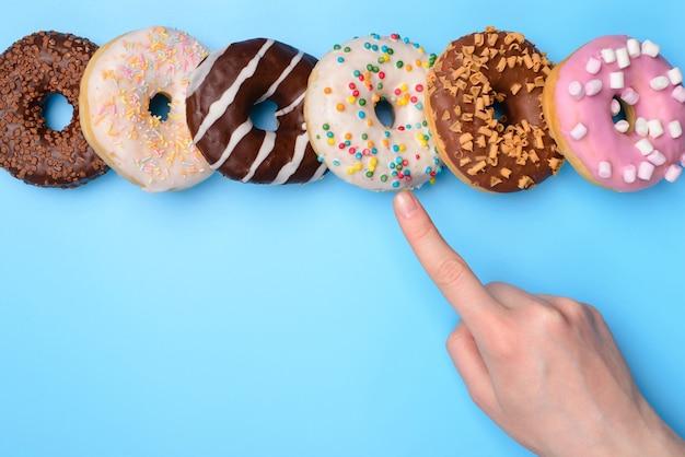 Hand die aangeeft met wijsvinger op donuts geïsoleerd op blauwe achtergrond