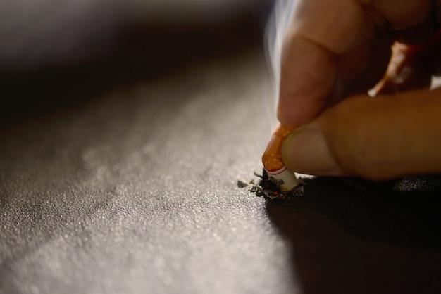 Hand die aangestoken sigaretuiteinde ter plaatse duwt