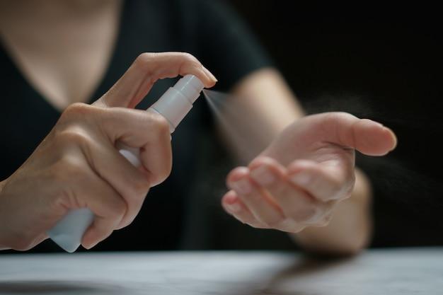 Hand die alcoholspray toepast voor coronavirus of covid-19-bescherming.