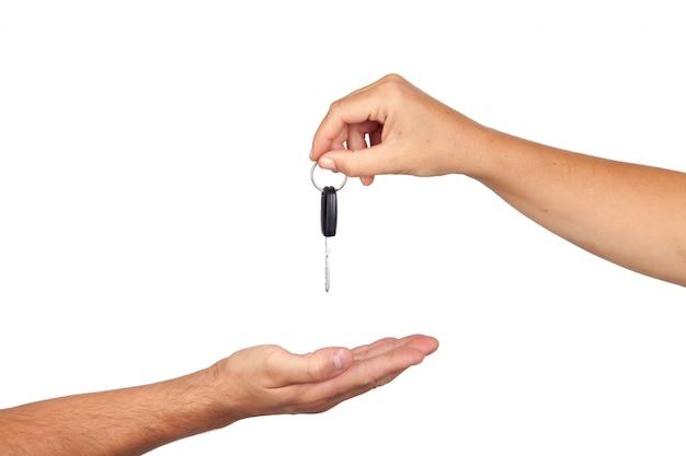 Hand die autosleutels geeft die op witte achtergrond worden geïsoleerd