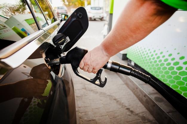 Hand die benzinepomp in autotank zet