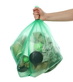 Hand die beschikbare zak met verschillend die afval houdt, op witte achtergrond wordt geïsoleerd