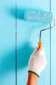 Hand die blauwe kleur op houten muur schildert