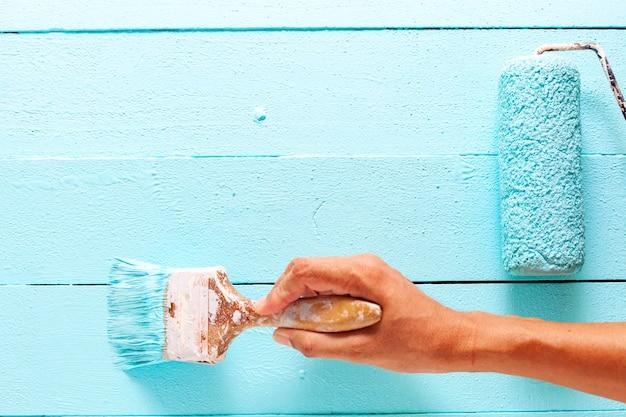Hand die blauwe kleur op witte houten plank schildert