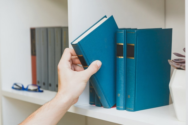 Hand die boek van de plank neemt