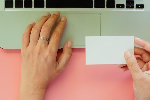 Hand die computerlaptop met behulp van en lege adreskaartjes op roze achtergrond houdt