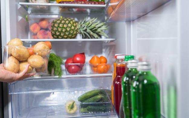 Hand die container met aardappelen uit de koelkast neemt