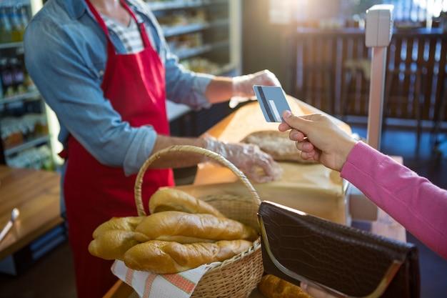 Hand die creditcard geeft bij betalingsteller