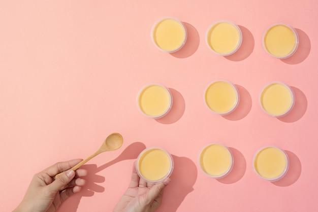Hand die crèmekaramel in minimalistische stijlopstelling op roze achtergrond zet