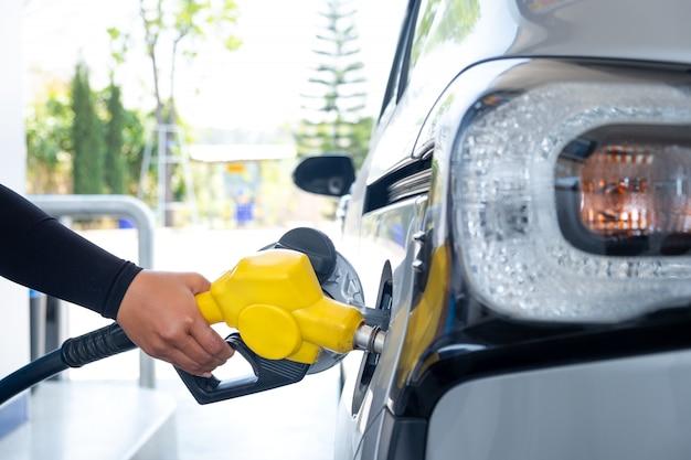 Hand die de auto met brandstof bij het benzinestation opnieuw vult