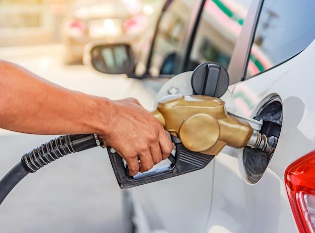 Hand die de auto opnieuw vullen met brandstof bij het benzinestation