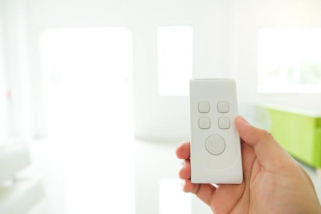 Hand die de elektronische afstandsbediening voor apparaat van het bevel slimme huis houdt.