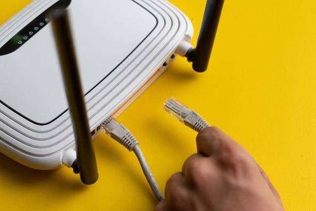 Hand die de ethernetkabel verbindt met een wifi-afstandsbedieningspunt