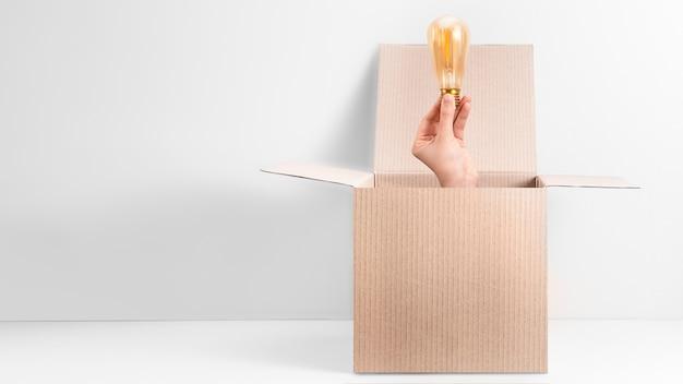 Hand die de gloeilamp van edison neemt uit de open kartondoos op witte achtergrond. wees anders, out of the box denkconcept.