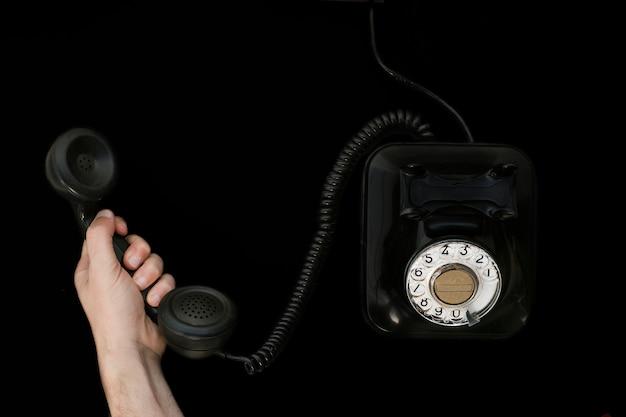 Hand die de handset van een oude telefoon grijpt