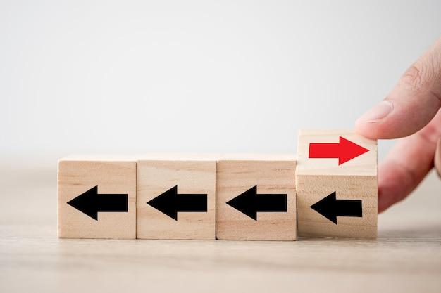 Hand die de houten pijl van het kubusblok van verandering van links naar rechts wegknipt voor bedrijfsverstoring en ander denkend idee.