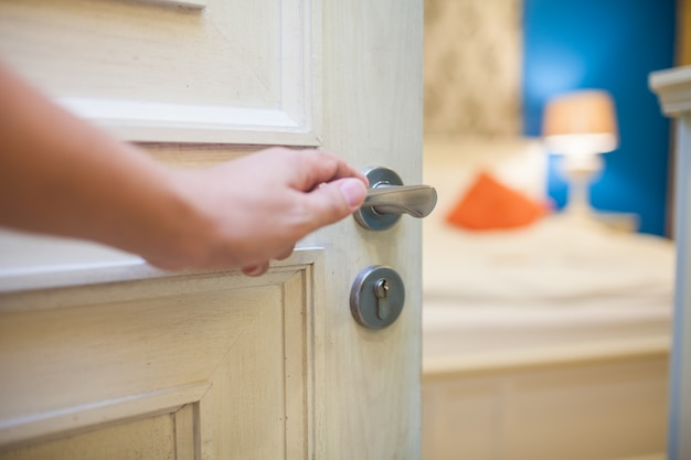 Hand die de slaapkamerdeur voor hotel en huisconcept opent