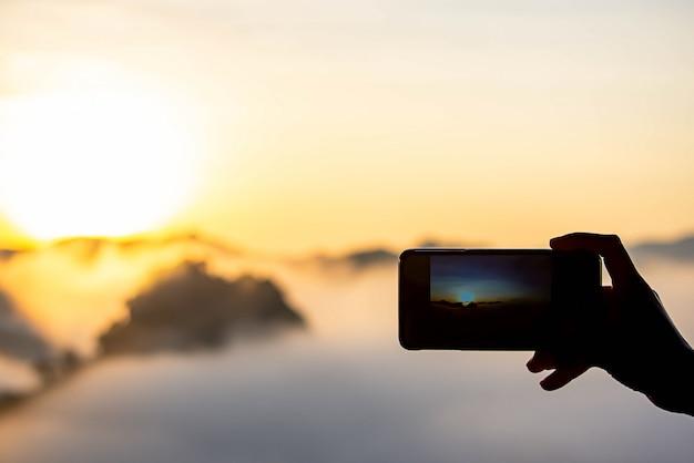 Hand die de telefoon houdt die de ochtendzon en de mist schiet.