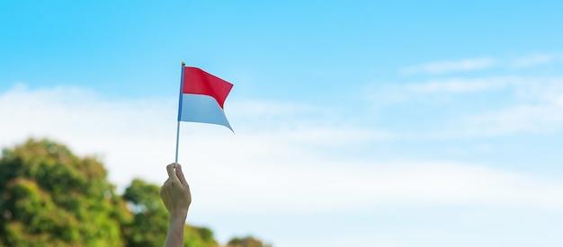 Hand die de vlag van indonesië op blauwe hemelachtergrond houdt. onafhankelijkheidsdag indonesië, nationale feestdag en gelukkige vieringsconcepten
