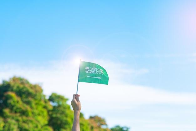 Hand die de vlag van saudi-arabië op blauwe hemelachtergrond houdt. nationale dag van september saoedi-arabië en gelukkige vieringsconcepten