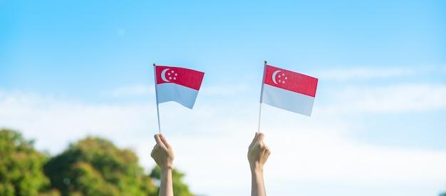 Hand die de vlag van singapore op blauwe hemelachtergrond houdt. nationale feestdag singapore en concepten voor gelukkige vieringen