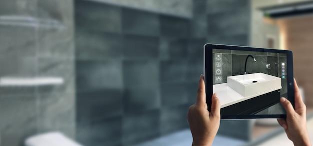 Hand die digitale tablet in de badkamers houdt